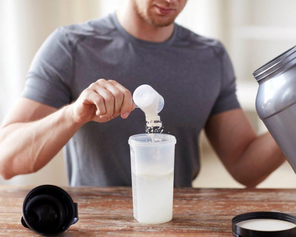 άντρας πίνει πρωτεΐνη whey σε shaker μετά την προπόνηση