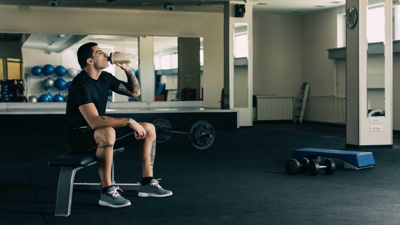 άντρας πίνει πρωτεΐνη μέσα στο γυμναστήριο